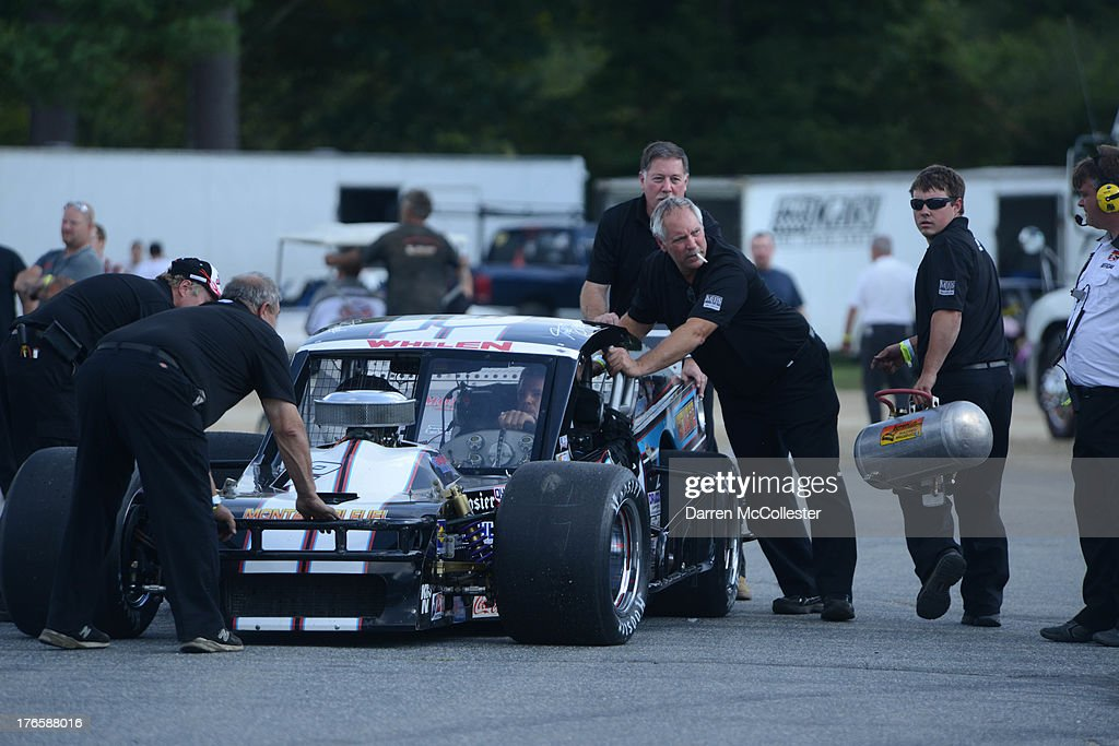 Pit crews push the #2 Dunleavy Repair/Montanari Fuel Ford driven by Todd Szegedy prior to qualifying at the Budweiser King of Beers 150 at Thompson Speedway August 15, 2013 in Thompson, Connecticut.