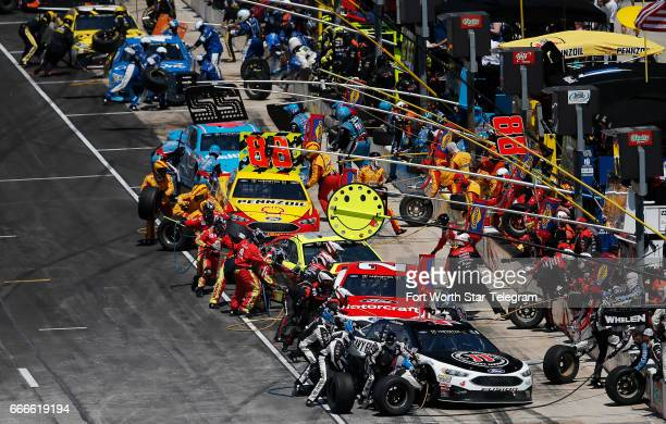Pit crews rush to service their cars during the O'Reilly Auto Parts 500 on Sunday April 9 2017 at Texas Motor Speedway in Fort Worth Texas