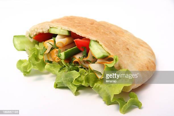 Pita bread stuffed by turkey pastrami and fresh salad