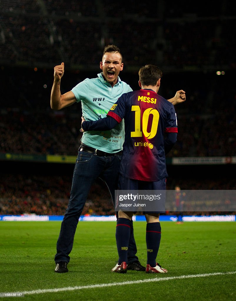 A pitch invader celebrates after embraces <a gi-track='captionPersonalityLinkClicked' href=/galleries/search?phrase=Lionel+Messi&family=editorial&specificpeople=453305 ng-click='$event.stopPropagation()'>Lionel Messi</a> of Barcelona during the la Liga match between FC Barcelona and Club Atletico de Madrid at the Camp Nou stadium on December 16, 2012 in Barcelona, Spain.