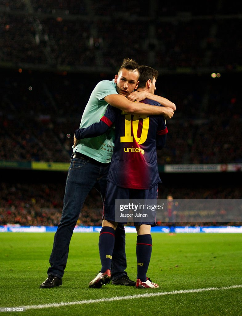 A pitch invader embraces <a gi-track='captionPersonalityLinkClicked' href=/galleries/search?phrase=Lionel+Messi&family=editorial&specificpeople=453305 ng-click='$event.stopPropagation()'>Lionel Messi</a> of Barcelona during the la Liga match between FC Barcelona and Club Atletico de Madrid at the Camp Nou stadium on December 16, 2012 in Barcelona, Spain.