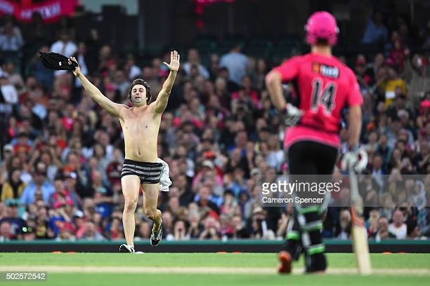 A pitch invader enters the field of play during the Big Bash League match between the Sydney Sixers and the Melbourne Stars at Sydney Cricket Ground...