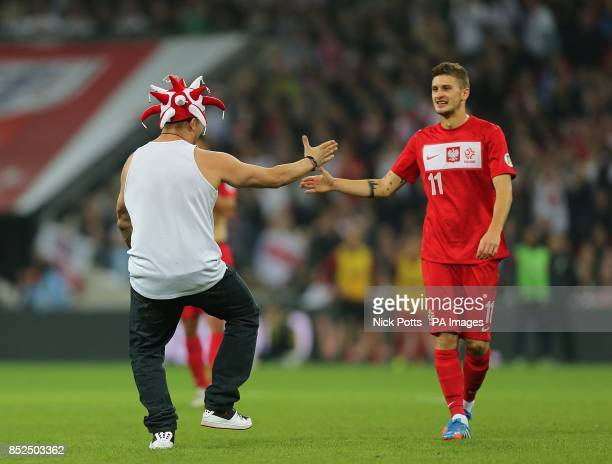 A pitch invader high fives Poland's Mateusz Klich after running onto the pitch