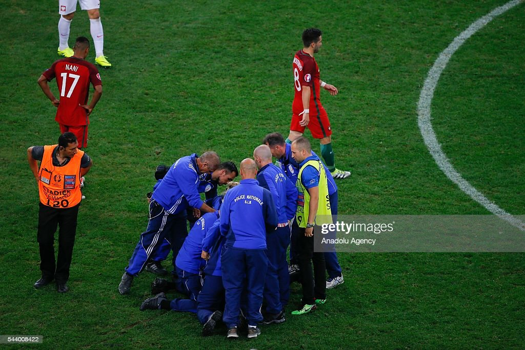 A pitch invader is carried off the pitch by French police during the Euro 2016 quarter-final football match between Poland and Portugal at the Stade Velodrome in Marseille, France on June 30, 2016.