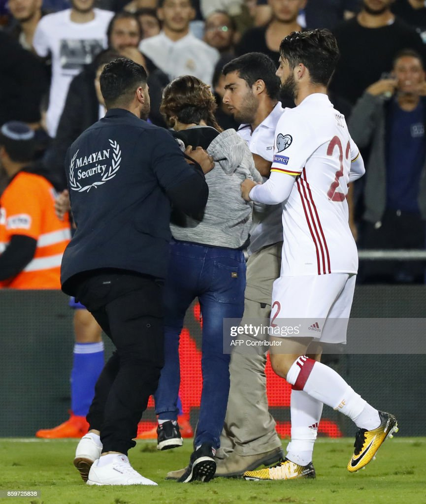 A pitch invader is detained by securiy during the Russia 2018 FIFA World Cup European Group G qualifying football match between Israel and Spain at Teddy Stadium in Jerusalem on October 9, 2017. Israeli police denied local media reports that the pitch invader who ran towards Spanish attacker Isco during a World Cup qualifier was carrying a knife. The Israeli news website Ynet cited security officials in the stadium as saying six fans entered the field at the end of the game, with one of them carrying a small knife in his sock. PHOTO / Jack GUEZ