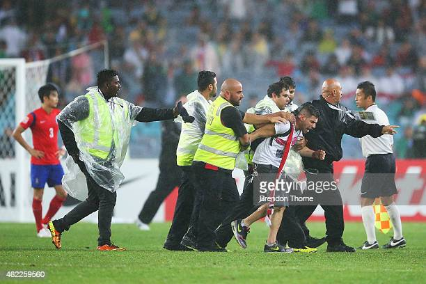 A pitch invader is escorted from the field by security during the Asian Cup Semi Final match between Korea Republic and Iraq at ANZ Stadium on...