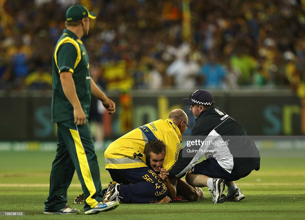 A pitch invader is grabbed by security during game one of the Commonwealth Bank One Day International series between Australia and Sri Lanka at Melbourne Cricket Ground on January 11, 2013 in Melbourne, Australia.