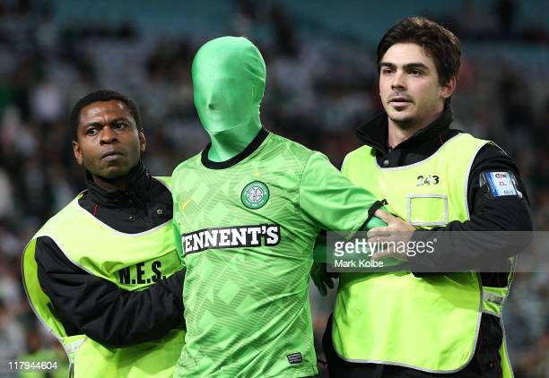 A pitch invader is removed from the field by security during the international friendly club match between the Central Coast Mariners and Glasgow...