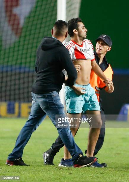 A pitch invader is stopped by security guards during a match between River Plate and Lanus as part of Supercopa Argentina 2017 at Ciudad de La Plata...