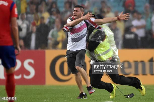 A pitch invader is stopped by security in the game between South Korea and Iraq in their AFC Asian Cup semifinal football match in Sydney on January...
