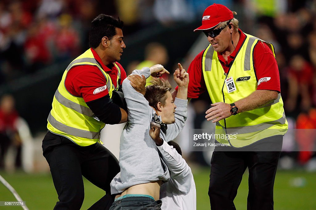 A pitch invader is tackled by security staff during the 2015/16 A-League Grand Final match between Adelaide United and the Western Sydney Wanderers at Adelaide Oval on May 1, 2016 in Adelaide, Australia.