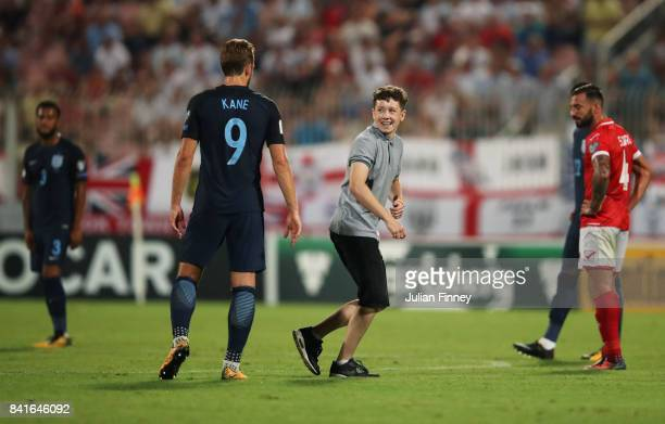A pitch invader smiles at Harry Kane of England during the FIFA 2018 World Cup Qualifier between Malta and England at Ta'Qali National Stadium on...