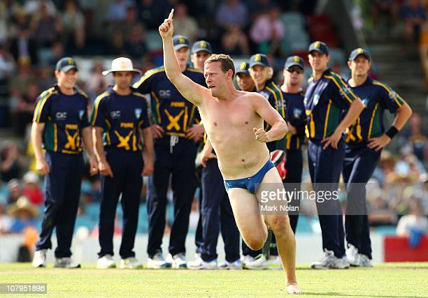 A pitch invader steals a bail during the tour match between the Australian PM's XI and England at Manuka Oval on January 10 2011 in Canberra Australia