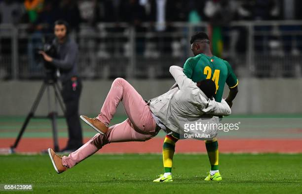 A pitch invader tackles Lamine Gassama of Senegal during the International Friendly match between the Ivory Coast and Senegal at the Stade Charlety...