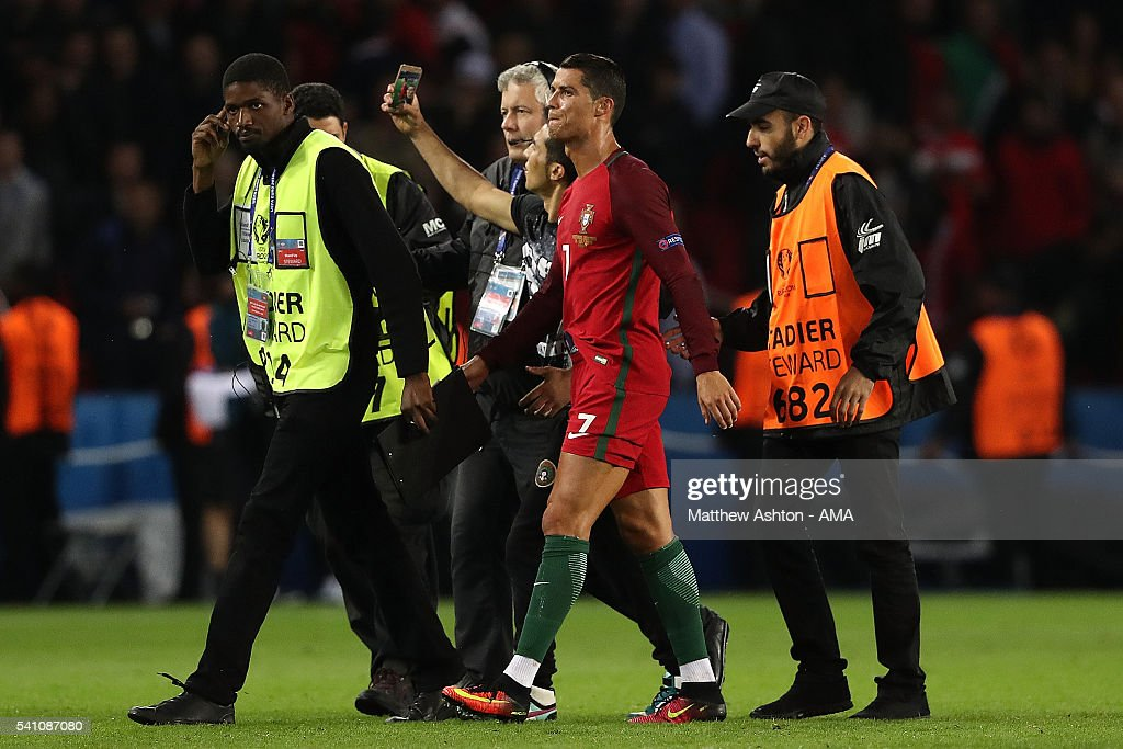 A pitch invader takes a selfie with Cristiano Ronaldo of Portugal at the end of the UEFA EURO 2016 Group F match between Portugal and Austria at Parc des Princes on June 18, 2016 in Paris, France.
