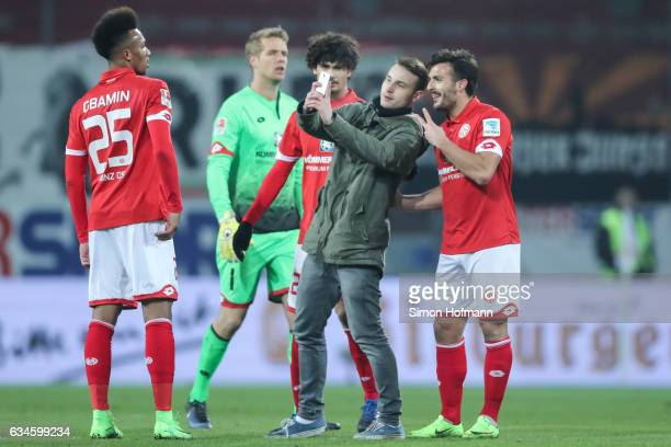A pitch invader takes a selfie with Giulio Donati of Mainz during the Bundesliga match between 1 FSV Mainz 05 and FC Augsburg at Opel Arena on...