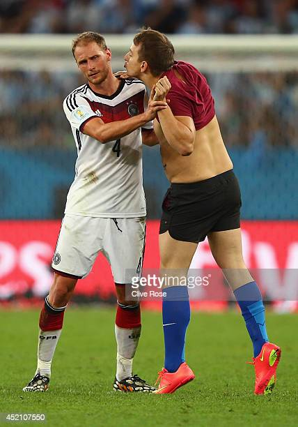 A pitch invader tries to kiss Benedikt Hoewedes of Germany during the 2014 FIFA World Cup Brazil Final match between Germany and Argentina at...