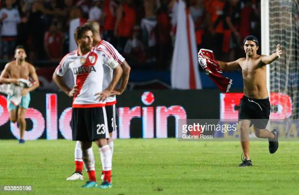 A pitch invader walks on the field during a match between River Plate and Lanus as part of Supercopa Argentina 2017 at Ciudad de La Plata Stadium on...