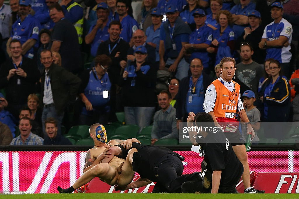 A pitch invader with Highlander face paint is is tackled to the ground by security during the round 15 Super Rugby match between the Western Force and the Highlanders at nib Stadium on May 25, 2013 in Perth, Australia.