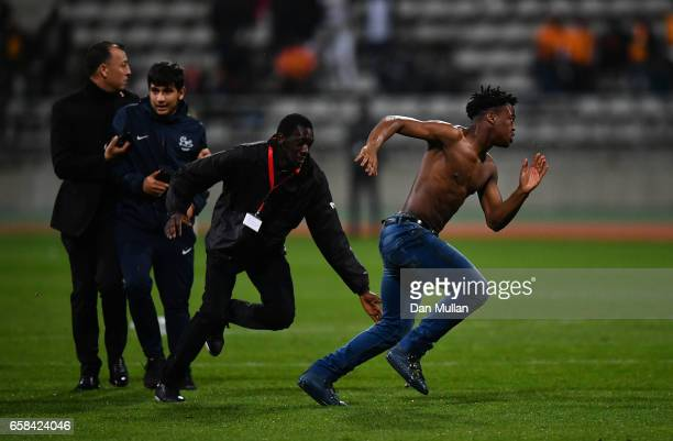 Pitch invaders are tackled by security during the International Friendly match between the Ivory Coast and Senegal at the Stade Charlety on March 27...