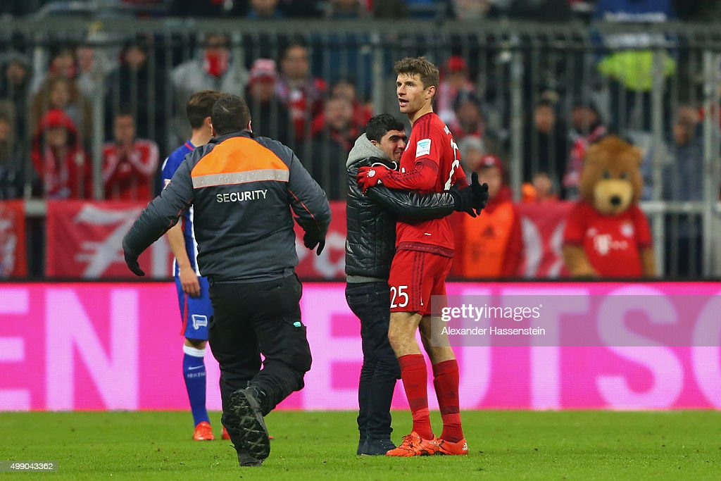 A pitch invaders hughs Thomas Mueller of Muenchen during the Bundesliga match between FC Bayern Muenchen and Herha BSC Berlin at Allianz Arena on November 28, 2015 in Munich, Germany.