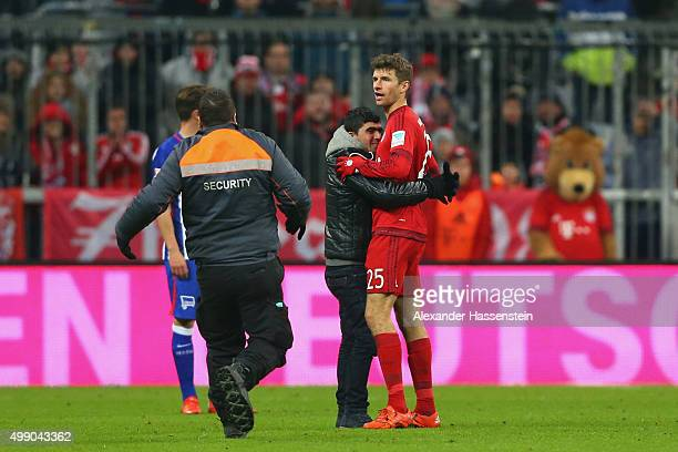 A pitch invaders hughs Thomas Mueller of Muenchen during the Bundesliga match between FC Bayern Muenchen and Herha BSC Berlin at Allianz Arena on...