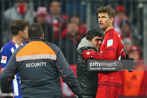 A pitch invaders hugs Thomas Mueller of Muenchen during the Bundesliga match between FC Bayern Muenchen and Herha BSC Berlin at Allianz Arena on...