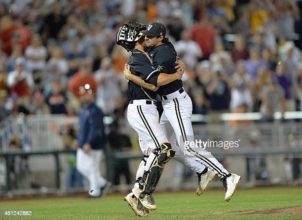 Pitcher Adam Ravenelle of the Vanderbilt Commodores jumps into the arms of catcher Robbie Coman and celebrate after beating the Virginia Cavaliers to...