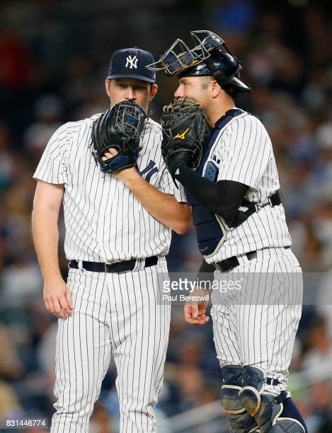 Pitcher Adam Warren of the New York Yankees talks with catcher Austin Romine of the New York Yankees on the mound in an MLB baseball game against the...