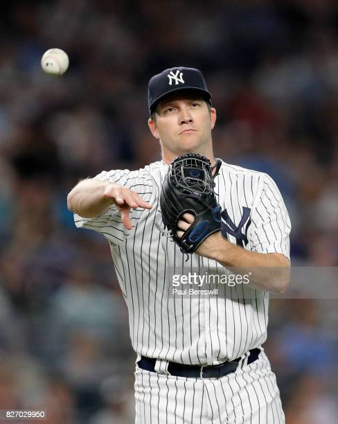 Pitcher Adam Warren of the New York Yankees throws to first base in an MLB baseball game against the Detroit Tigers on August 1 2017 at Yankee...