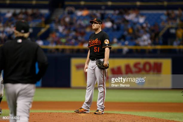 Pitcher Alec Asher of the Baltimore Orioles waits to be taken off the mound by manager Buck Showalter after walking Corey Dickerson of the Tampa Bay...