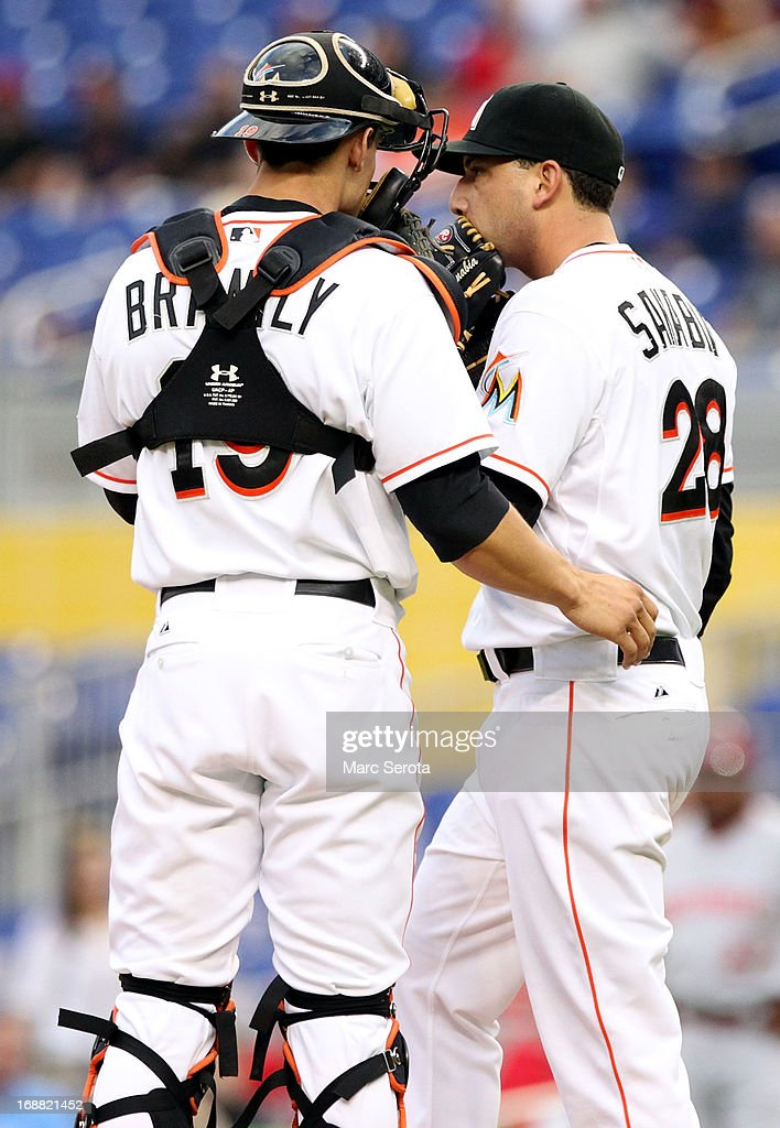 Pitcher Alex Sanabia #28 of the Miami Marlins chats with Catcher Rob Brantley #19 in the third inning against the Cincinnati Reds at Marlins Park on May 15, 2013 in Miami, Florida.