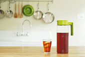 Pitcher and glass of iced tea on kitchen counter