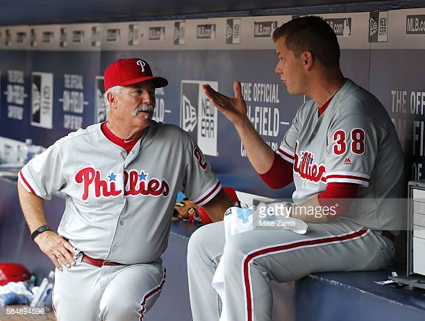 Pitcher Andrew Bailey of the Philadelphia Phillies talks with pitching coach Bob McClure in the dugout after giving up a 2run home run to Jeff...