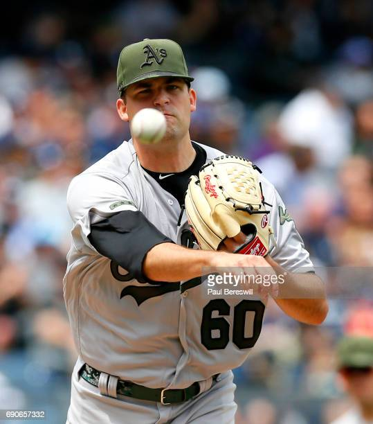 Pitcher Andrew Triggs of the Oakland Athletics throws to first on a pickoff attempt in an MLB baseball game against the New York Yankees on May 28...