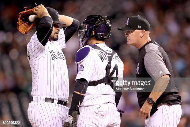 Pitcher Antonio Senzatela of the Colorado Rockies confers with catcher Tony Wolters and pitching coach Steve Foster in the ninth inning against the...