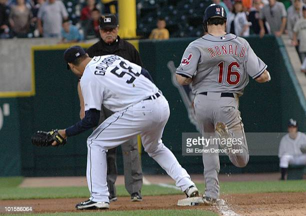 Pitcher Armando Galarraga of the Detroit Tigers covers first base as Jason Donald of the Cleveland Indians steps on the bag while umpire Jim Joyce...