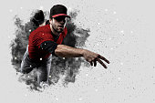 Pitcher Baseball Player with a red uniform coming out of a blast of smoke .