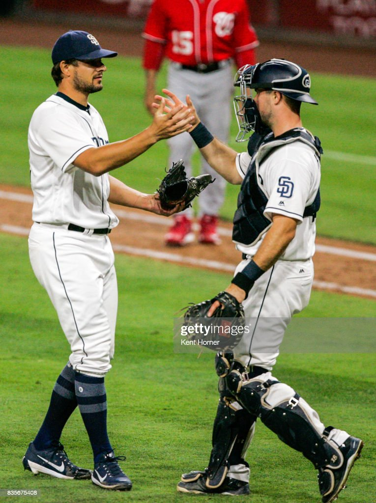 Pitcher Brad Hand #52 and catcher Austin Hedges #18 of the San Diego Padres celebrate after recording the final out of the 9th inning against the Washington Nationals at PETCO Park on August 19, 2017 in San Diego, California.