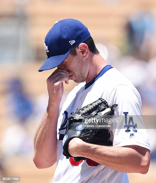 Pitcher Brandon McCarthy of the Los Angeles Dodgers reacts after wild pitch against Colorado Rockies during the second inning of the baseball game at...