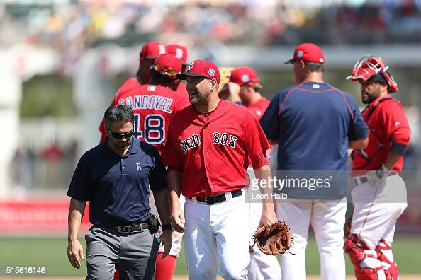 Pitcher Brian Johnson of the Boston Red Sox walks off the mound with the team trainer during the fifth inning of the Spring Training Game against the...