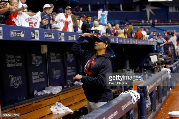 Pitcher Carlos Carrasco of the Cleveland Indians signs autographs for fans following the Indians' 50 win over the Tampa Bay Rays at a game on August...