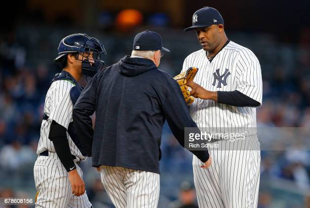 Pitcher CC Sabathia of the New York Yankees is visited on the mound by Larry Rothschild as catcher Kyle Higashioka looks on during the fifth inning...