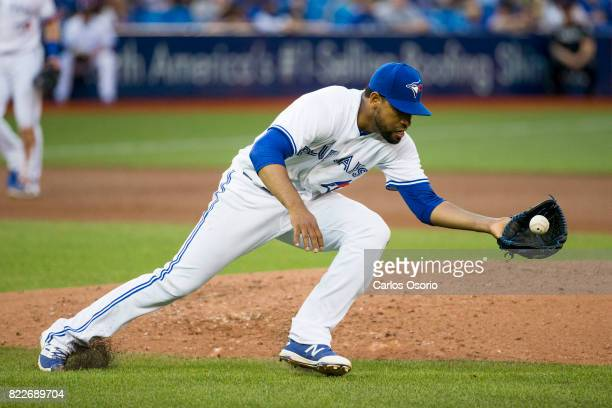 TORONTO ON JULY 25 Pitcher Cesar Valdez of the Blue Jays fields a ball after getting hit with a comebacker during the 4th inning of MLB action as the...