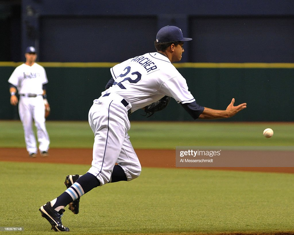 Pitcher Chris Archer #22 of the Tampa Bay Rays tosses a ball for a put out at 1st base against the Texas Rangers September 18, 2013 at Tropicana Field in St. Petersburg, Florida.