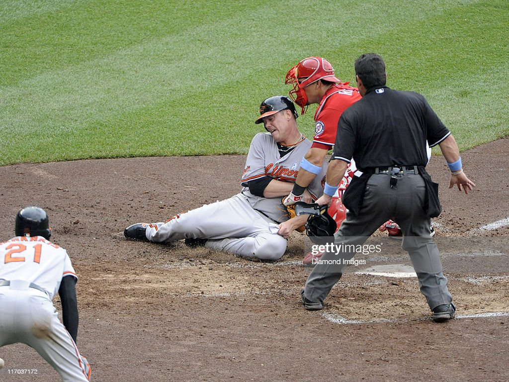 Pitcher Chris Jakubauskas of the Baltimore Orioles is tagged out at homeplate by catcher Wilson Ramos of the Washington Nationals during the top of...