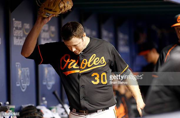 Pitcher Chris Tillman of the Baltimore Orioles throws his glove to the ground in the dugout after being taken out of the game during the eighth...