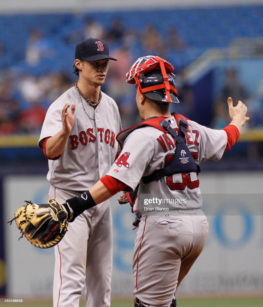 Pitcher Clay Buchholz #11 of the Boston Red Sox and catcher Christian Vazquez #55 celebrate their 3-0 win over the Tampa Bay Rays following a game on August 31, 2014 at Tropicana Field in St. Petersburg, Florida.