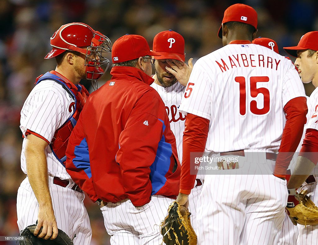 Pitcher Cliff Lee #33 of the Philadelphia Phillies, center, reacts to a visit by pitching coach Rich Dubee #30, catcher Erik Kratz #31 and John Mayberry #15 during the third inning against the St. Louis Cardinals in a MLB baseball game on April 20, 2013 at Citizens Bank Park in Philadelphia, Pennsylvania. The Cardinals defeated the Phillies 5-0.