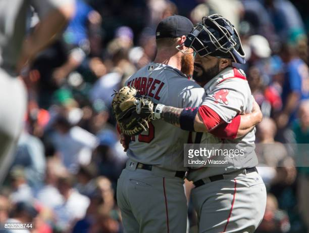 Pitcher Craig Kimbrel of the Boston Red Sox gets a hug from catcher Sandy Leon after striking out Carlos Ruiz of the Seattle Mariners to win the game...